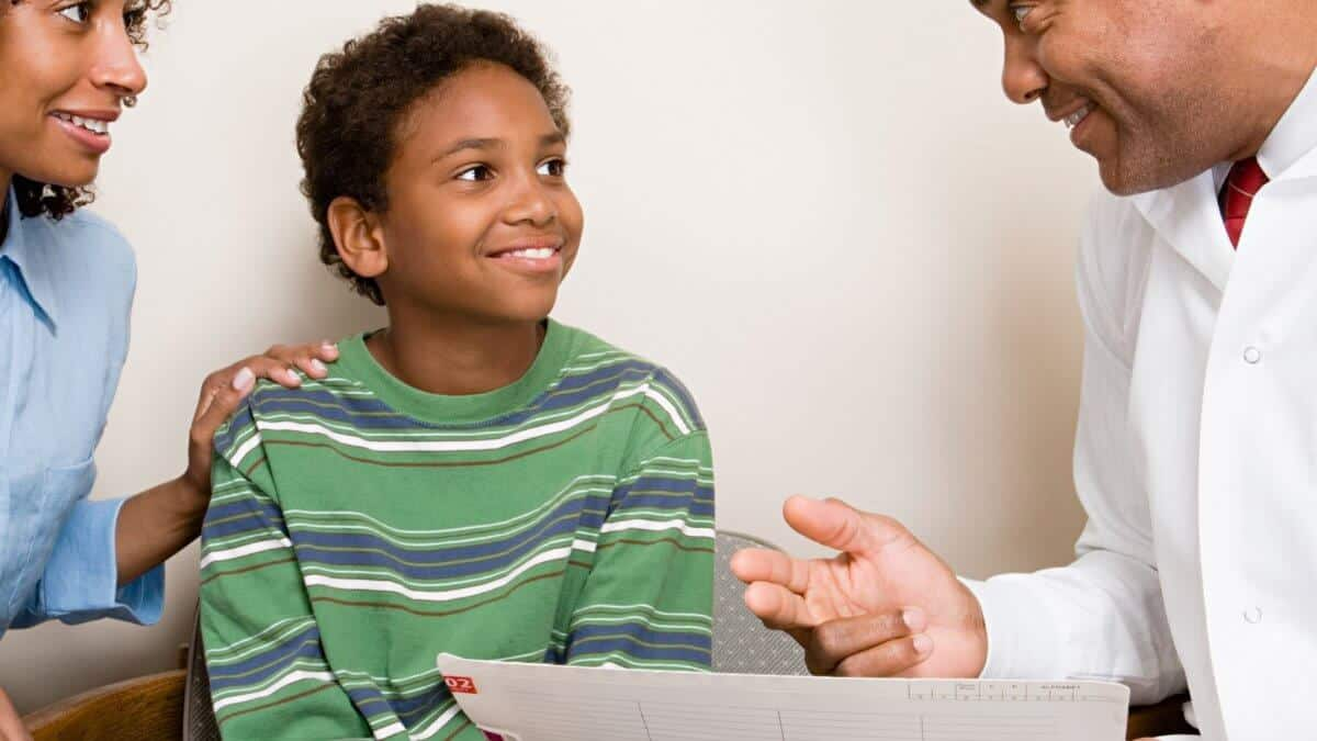 Dentist consulting with child and parent