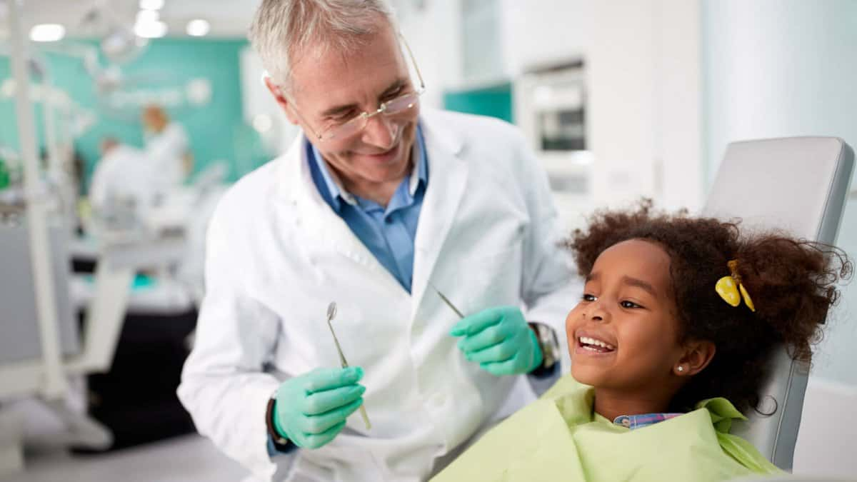 Young girl sitting in dental chair with dentist