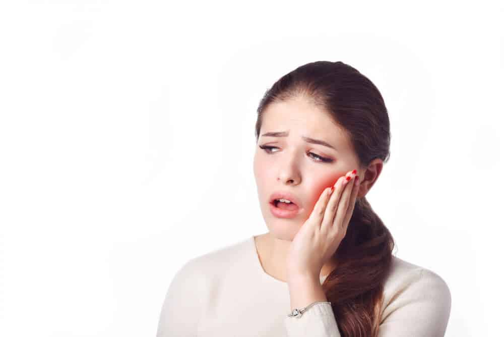 person holding her jaw from pain