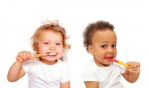 two kids brushing their teetht