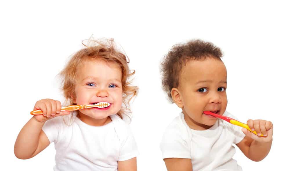 two kids brushing their teetht