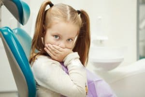A little girl who is scared of the dentist and covering her mouth