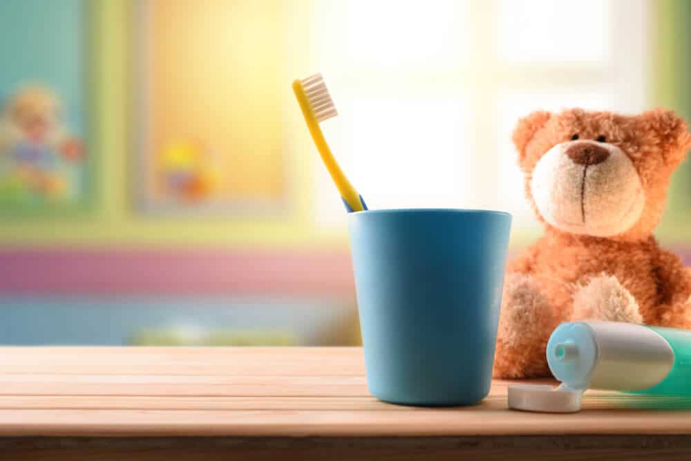 A stuffed bear next to a tooth brush and toothpaste to bring to the child's dental office