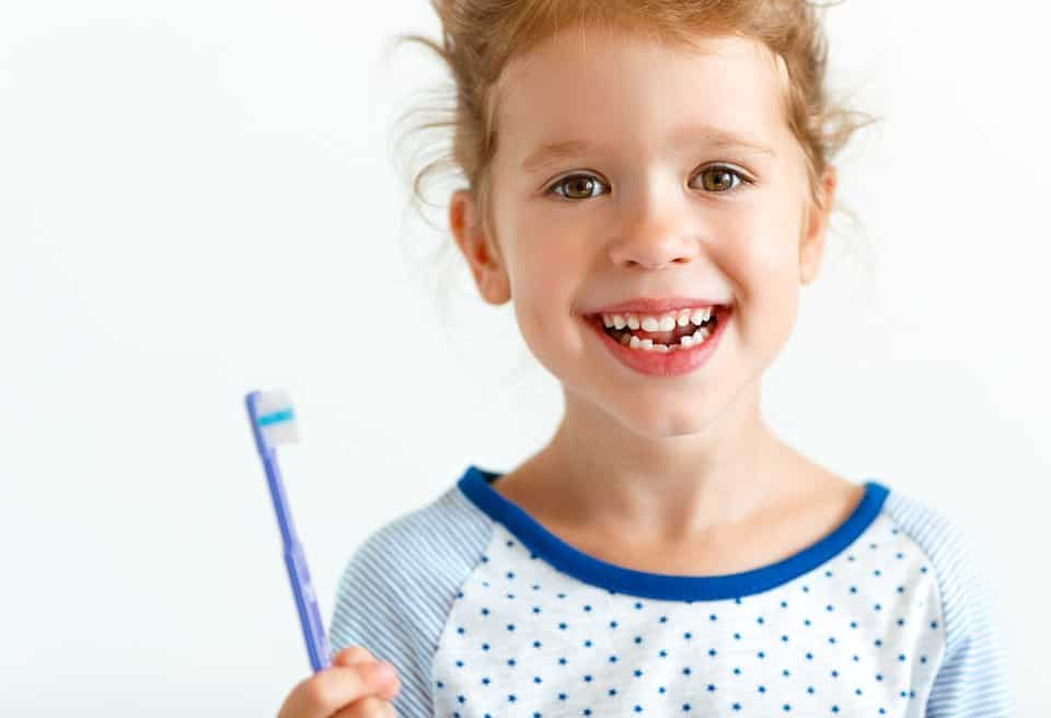 A little girl with a healthy smile holding a toothbrush