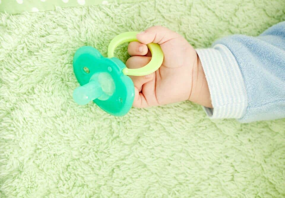 A baby holding a pacifier