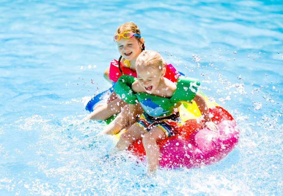 Kids playing in the pool & splashing on a tube
