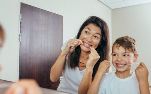 Parent teaches child to floss to fight gingivitis