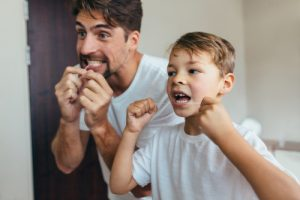 a father teaching his son to floss